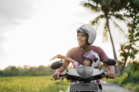 asian father and child  ride motorcycle scooter