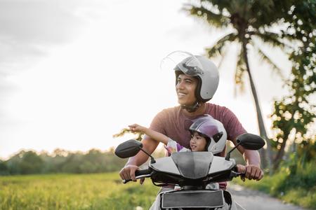 Un père et un enfant asiatiques montent un scooter de moto