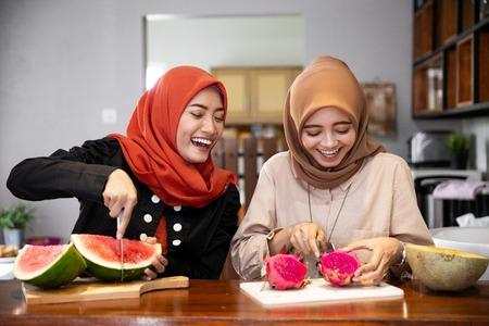 Amie musulmane préparant un cocktail de dessert aux fruits Banque d'images