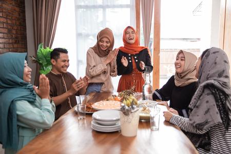 amigo musulmán y familia riendo juntos durante el almuerzo. Foto de archivo