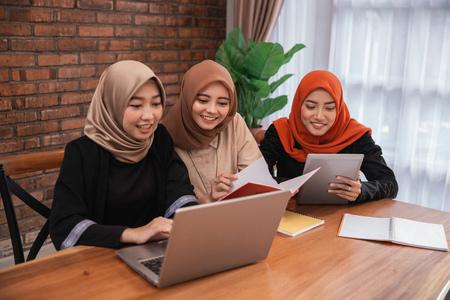 Schüler diskutieren gemeinsam mit Laptop