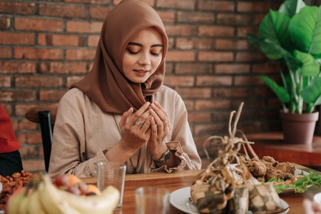 woman open her palm and pray before eating
