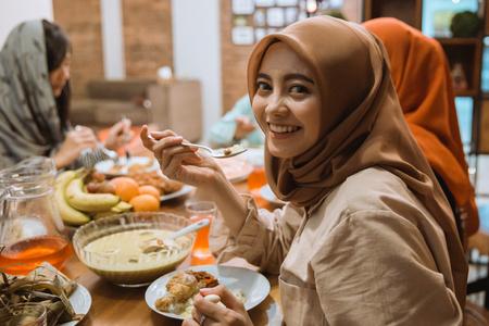 moslimvrouw die lacht tijdens het eten Stockfoto