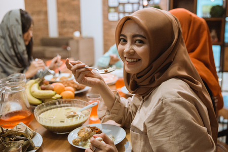 muslim woman smiling while dinner Stock Photo