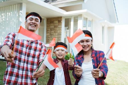 famiglia che tiene una bandiera dell'indonesia. festeggiare l'indipendenza