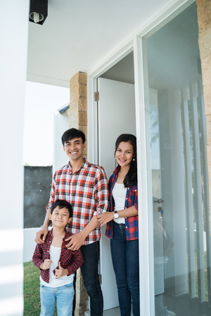 asian family in front of the door of their house