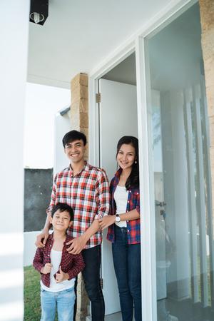 familia asiática frente a la puerta de su casa