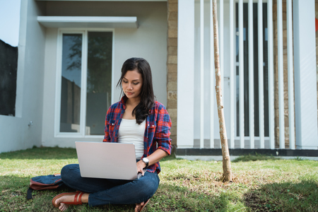 portrait of female asian student using laptop in the park Stock Photo - 121438505