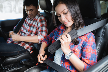 couple fasten seatbelt on before going by car