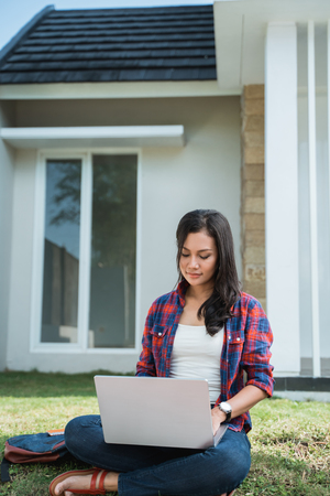 portrait of female asian student using laptop in the park Stock Photo - 121558704