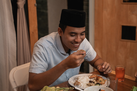 young muslim man eating dinner with family 版權商用圖片