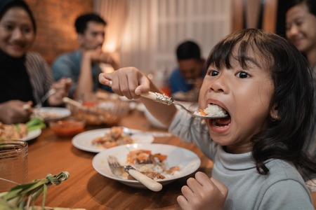 child daughter eating by herself during dinner 免版税图像 - 121358065