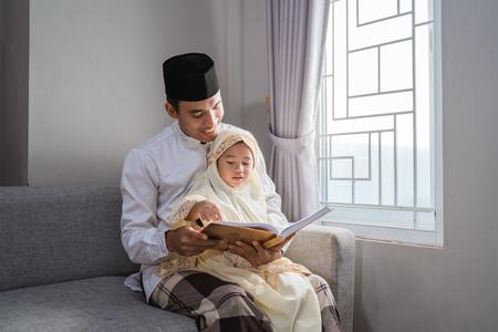 padre musulmán lee el corán con su hija Foto de archivo