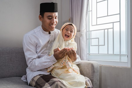muslim father and kid praying together