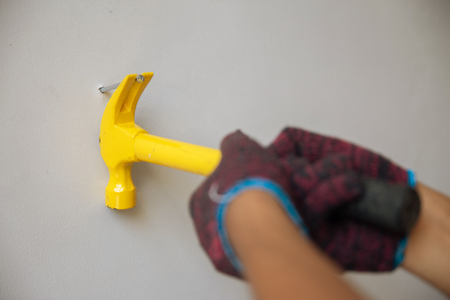 Close up hands with gloves hammering a nail Imagens