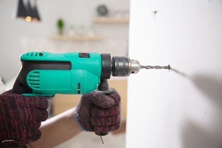 hands with gloves using electric drill Banque d'images