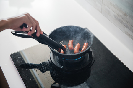 hands using food tongs to frying sausages