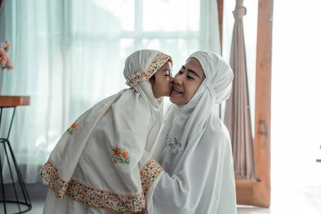 moslim jong kind kust haar moeder na het bidden