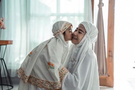 muslim young child kiss her mom after praying Stockfoto - 122175077