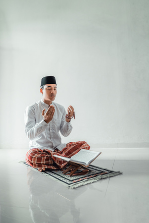 muslim asian man praying to god