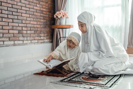 madre e figlio che leggono il corano