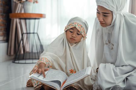 moslimouder en dochter die koran lezen
