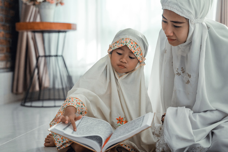 muslim parent and daughter reading quran