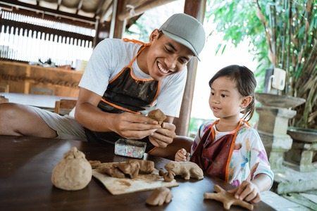 asian father and daughter working with clay Imagens