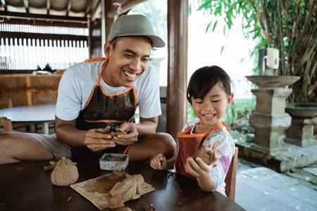 padre e figlia asiatici che lavorano con l'argilla