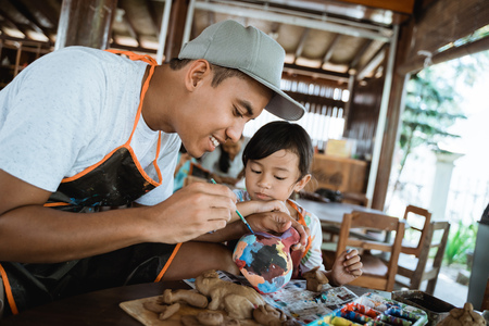 father and child painting pottery goods 版權商用圖片