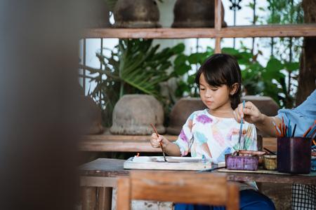 child painting on white fabric