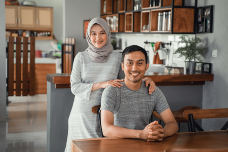 muslim couple sitting in dining room together Banco de Imagens
