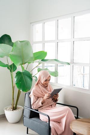 femme musulmane naviguant avec une tablette tout en se relaxant