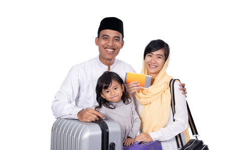 muslim family with suitcase isolated over white background Foto de archivo