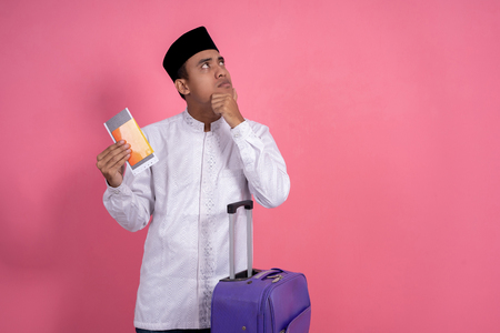 man with suitcase and passport thinking