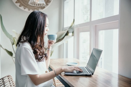 asian woman drinking coffee while working herself in cafe Stockfoto