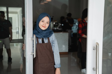 friendly asian beautiful muslim woman welcoming guest to the shop