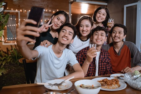 asian bestfriend group take selfie with smartphone while having garden party 版權商用圖片 - 122811457