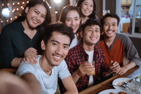 asian bestfriend group take selfie with smartphone while having garden party