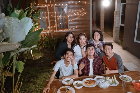 top view of young asian people enjoy their dinner in home backyard with friend