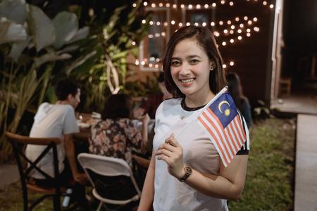 독립 기념일을 축하하는 동안 말레이시아 국기를 들고 아시아 여자