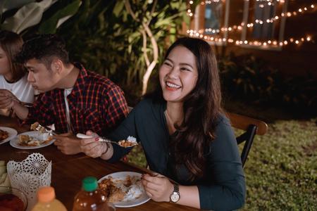 smiling asian woman enjoying their garden dinner party Stok Fotoğraf