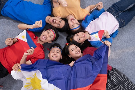 excited asian young supporter holding philippines flag Stock fotó