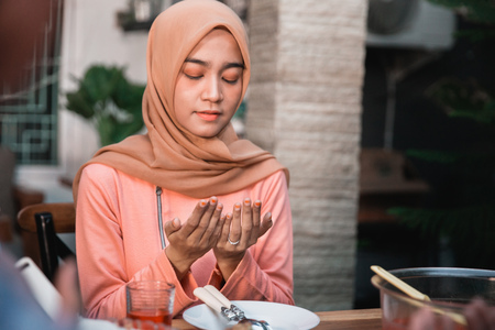 Hijab women pray together before meals