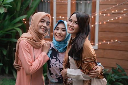 Three islam women standing on the backyard while look at camera