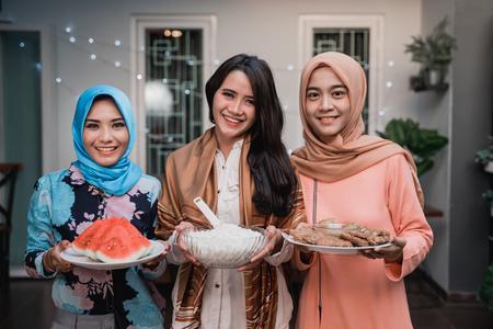 three hijab woman preparing food to serve when breaking fast Stockfoto