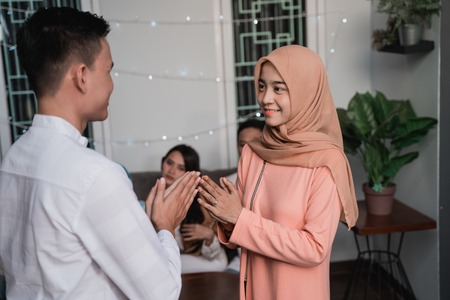asian man and hijab woman greet each other apologizing Stock Photo