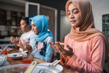 Hijab women and a man pray together before meals