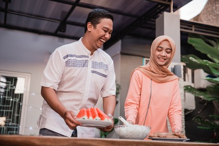 young hijab woman and boyfriend prepare cuisine for breaking fast serve to friends in the house at afternoon