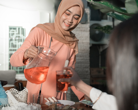 Hijab woman pours sweet drink in to a glass when break fast in the afternoon